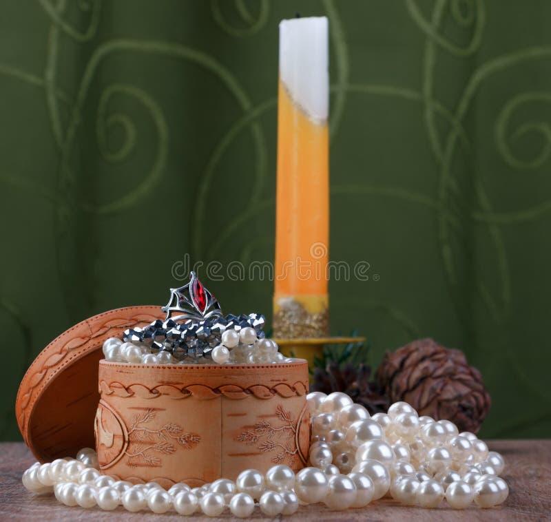 Kleine Birkenrindeschatulle umgeben durch Perlen auf Hintergrund der Kerze lizenzfreie stockfotos