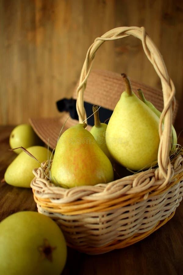 Kleine Birnen in einem Weidenkorb lizenzfreie stockfotografie