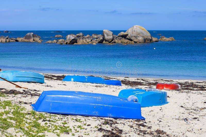 Kleine blaue Boote auf dem leeren Strand stockbilder