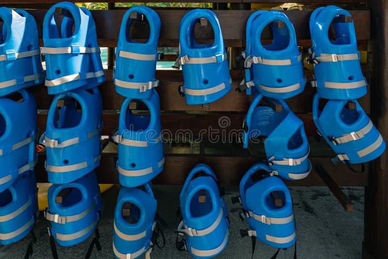 Kleine blaue Schwimmwesten für Kinder hängen in der Reihe am poo stockfoto