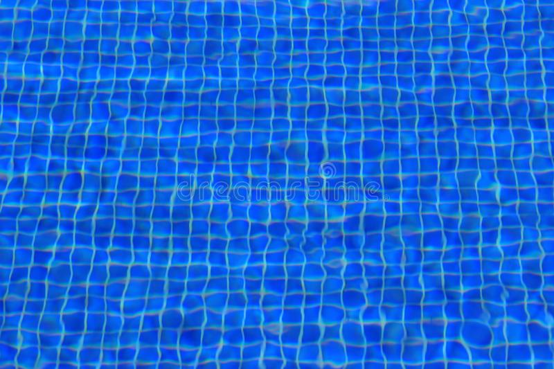 Kleine blauwe die pooltegels lichtjes door rimpelingen in het water worden gestoord stock afbeelding