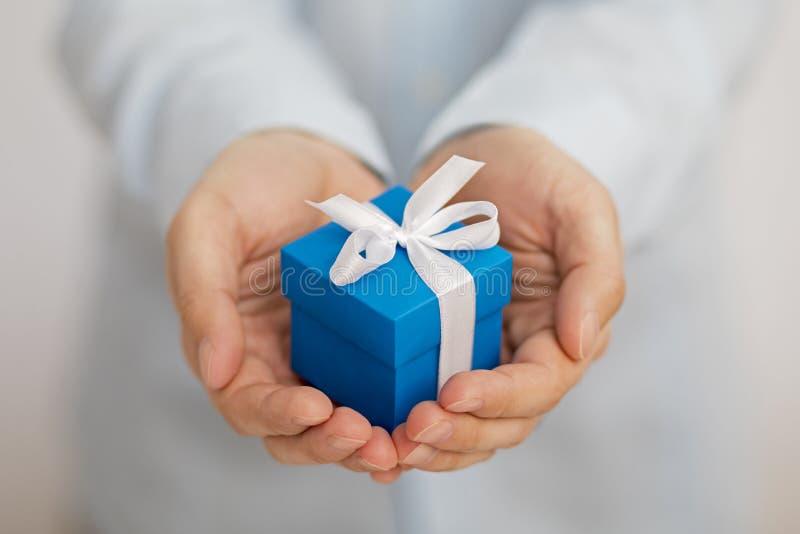 Kleine blauwe huidige doos in handen stock foto's