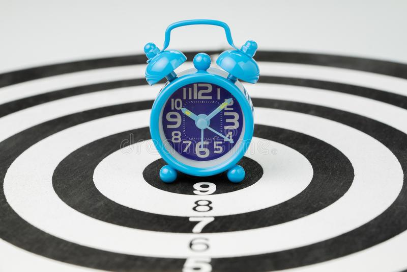Kleine blauwe retro wekker bij de centrumpot van zwart-wit cirkeldartboard die als tijd, doel of bedrijfsdoel gebruiken met stock foto
