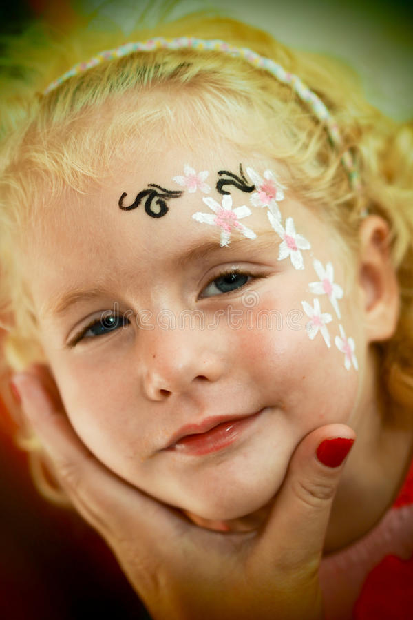 Kleine blonde blauäugige Mädchengesichtsmalerei lächelt stockbilder