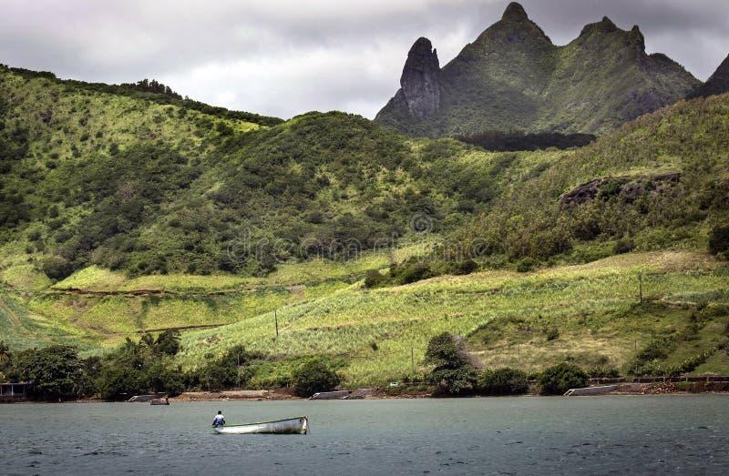 Kleine boatman die langs de groene bergachtige kust vissen royalty-vrije stock afbeeldingen