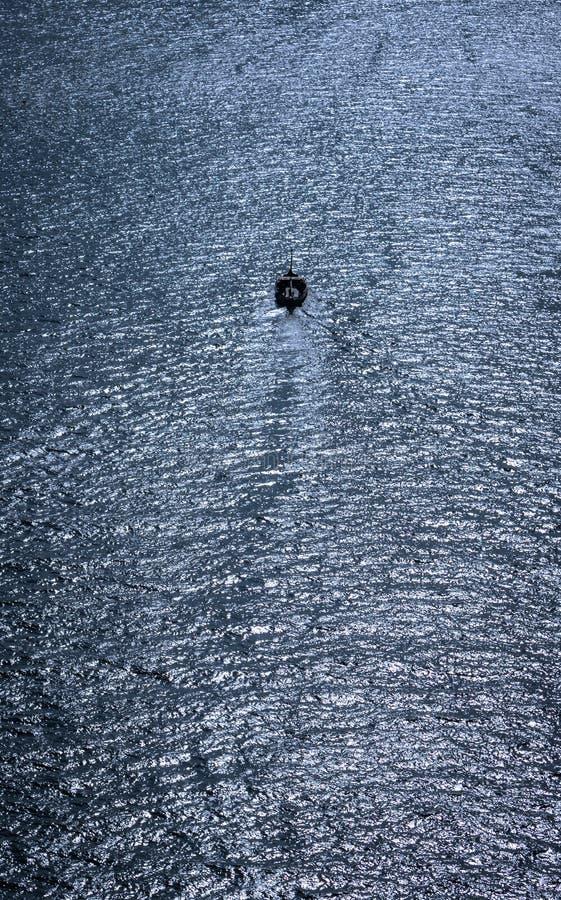 Kleine boot die uit in de reusachtigheid van het overzees vaart stock foto