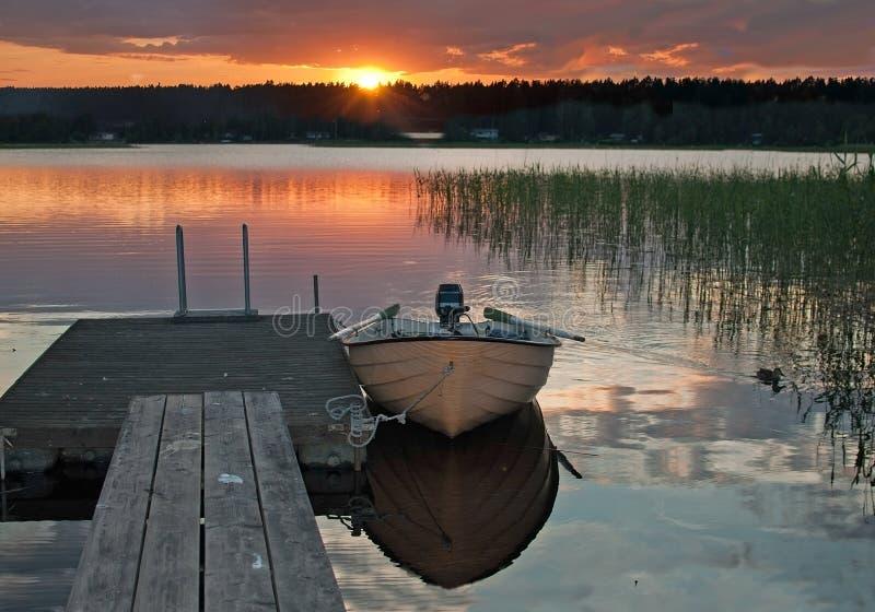 Kleine boot door houten pier wordt vastgelegd die royalty-vrije stock foto
