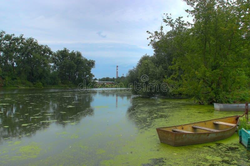 Kleine boot met de hemel bij rivier in het bos wordt weerspiegeld dat royalty-vrije stock foto