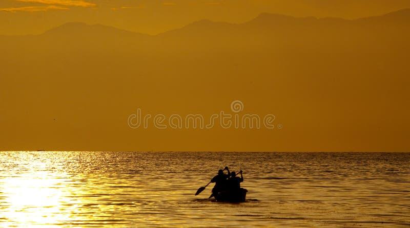 Kleine boot met de vissers die in de zonsondergang op het Kazinga-Kanaal varen afrika oeganda stock afbeeldingen