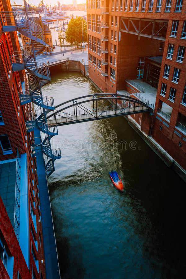 Kleine boot onder brug over kanaal tussen rode baksteengebouwen in het oude pakhuisdistrict Speicherstadt in Hamburg binnen royalty-vrije stock afbeelding