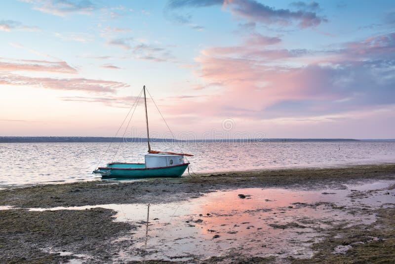 Kleine boot op het meer bij zonsondergang, dageraad stock foto's