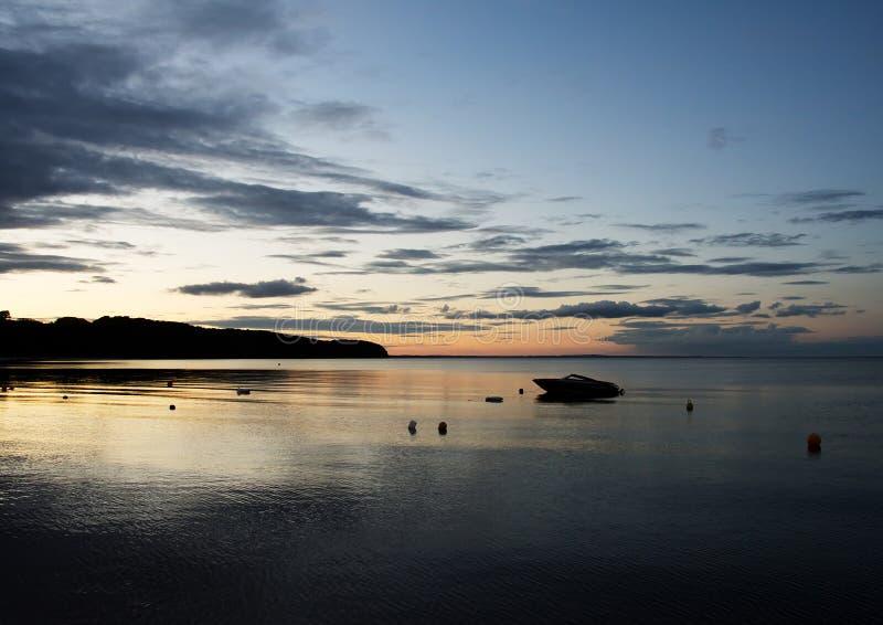 Kleine boot op zee bij zonsondergang dichtbij Middelfart, Denemarken stock afbeeldingen
