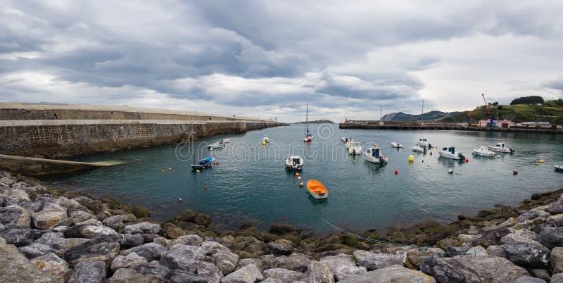 Kleine Boote am Eingang des Fischereihafens von Bermeo auf der Küste von Vizcaya an einem bewölkten Tag lizenzfreies stockfoto