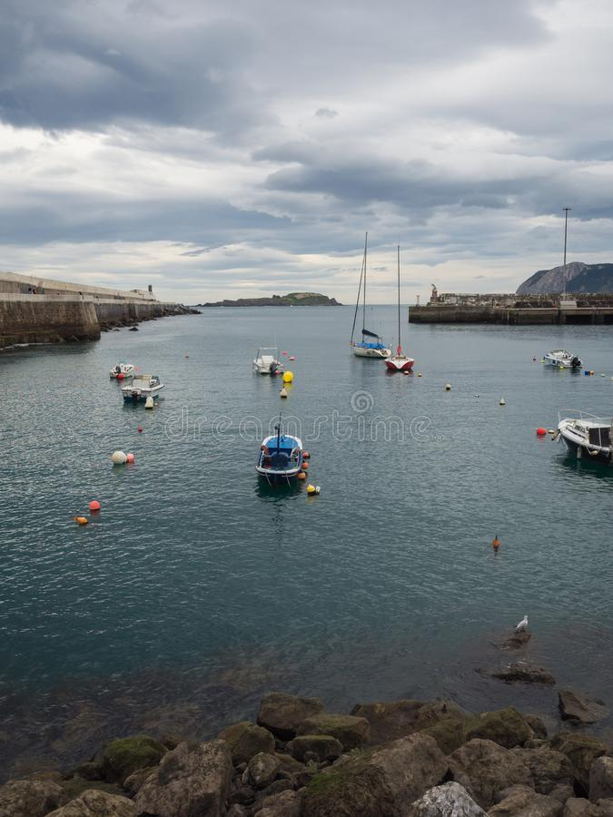 Kleine Boote am Eingang des Fischereihafens von Bermeo auf der Küste von Vizcaya an einem bewölkten Tag stockbild