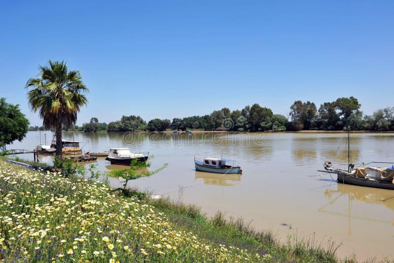 Kleine Boote am Pier auf dem Guadalquivir-Fluss, wie er durch Lederhäute del Provinz Rios, Sevilla überschreitet, Andalusien, Spa stockfotografie