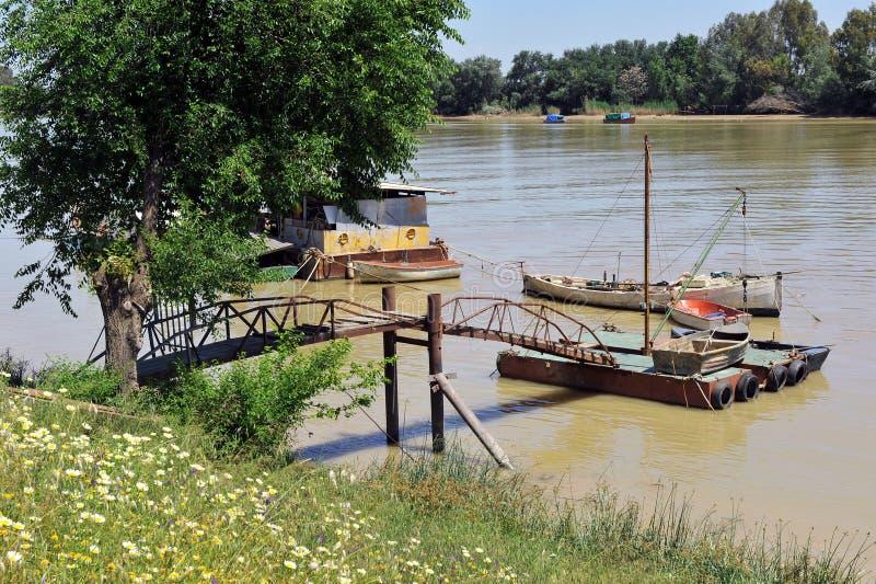 Kleine Boote am Pier, der Guadalquivir-Fluss, wie er durch Lederhäute del Provinz Rios, Sevilla überschreitet, Andalusien, Spanie lizenzfreies stockfoto