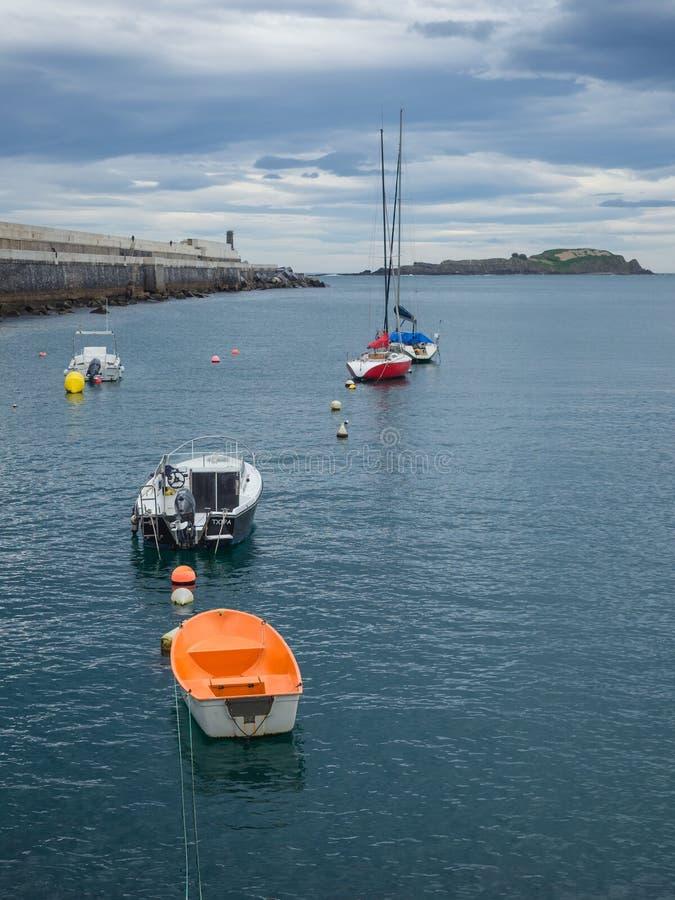 Kleine boten bij de ingang van de vissershaven van Bermeo op de kust van Biscaye op een bewolkte dag stock afbeeldingen