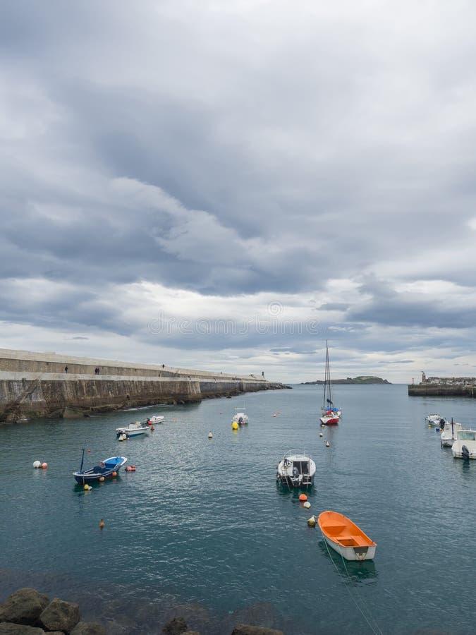 Kleine boten bij de ingang van de vissershaven van Bermeo op de kust van Biscaye op een bewolkte dag royalty-vrije stock foto