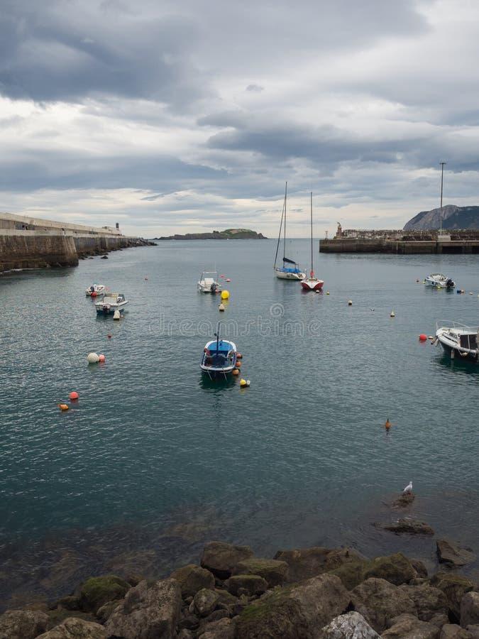 Kleine boten bij de ingang van de vissershaven van Bermeo op de kust van Biscaye op een bewolkte dag stock afbeelding
