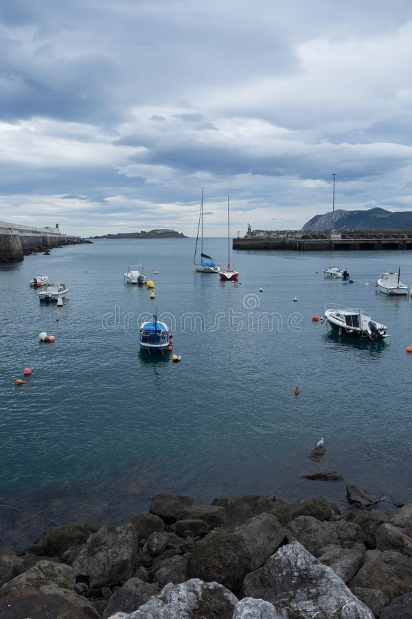 Kleine boten bij de ingang van de vissershaven van Bermeo op de kust van Biscaye op een bewolkte dag stock fotografie