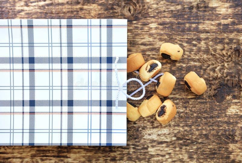 Kleine Brötchen mit dem Mohn verschüttet aus einer Papiertüte auf eine alte strukturierte Holzoberfläche heraus stockbild