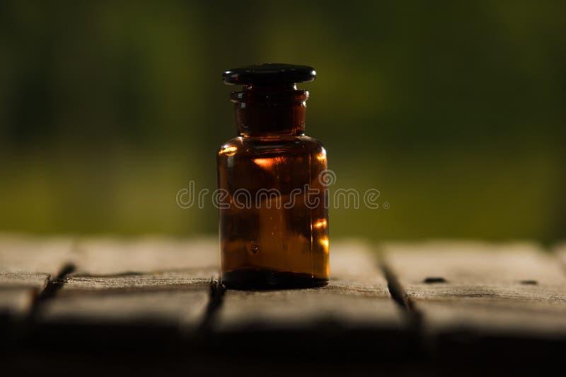 Kleine braune Medizinflasche für Magier beheben das Sitzen auf Holzoberfläche, schöne Nachtlichteinstellung, magisches Konzept stockfotografie
