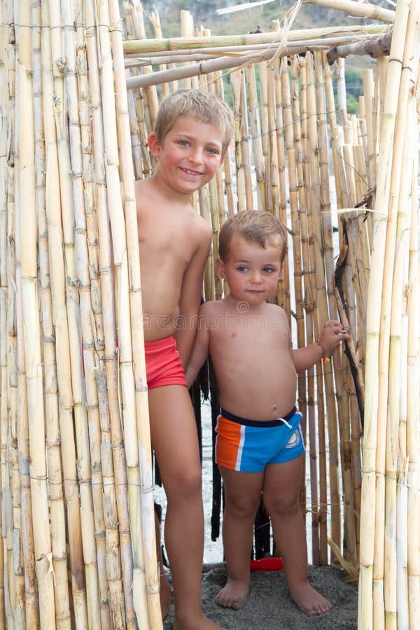 Kleine broers die op het strand in een bamboehut spelen royalty-vrije stock afbeeldingen