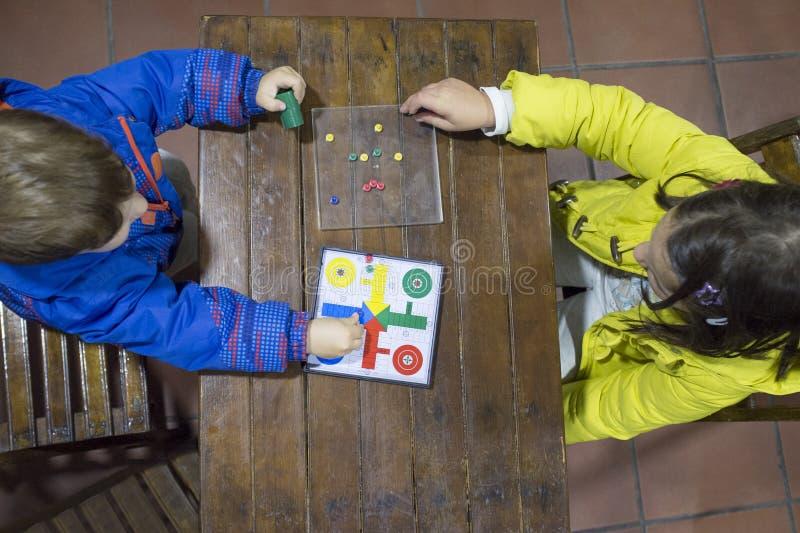Kleine broers die Parchis over houten uitstekende lijst spelen stock afbeeldingen
