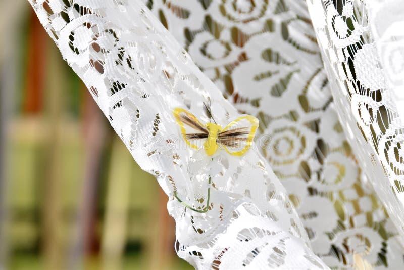 Kleine, bruine vlinder op een wit gordijn royalty-vrije stock afbeelding