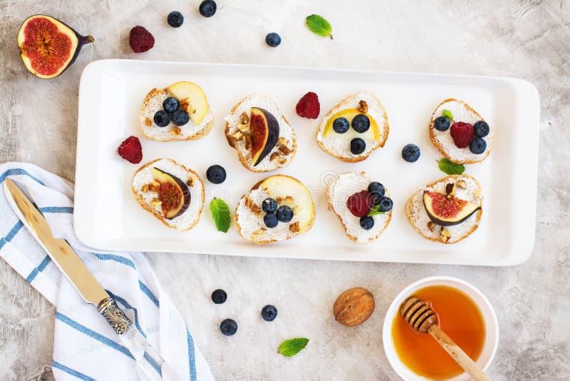 Kleine bruschetta met bessen, honing, ricotta en munt stock afbeelding
