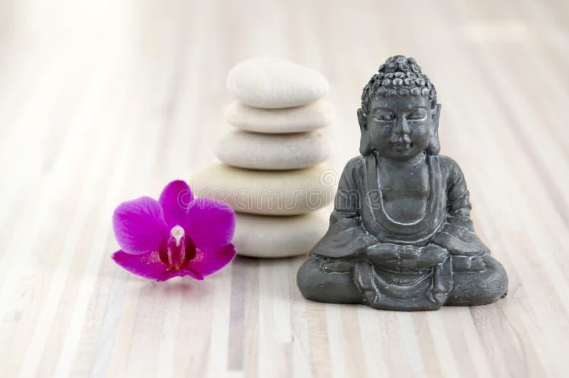 Kleine Buddha-Skulptur, Kiesel Steinhaufen, fünf weiße Steine, eine purpurrote Phalaenopsisorchideenblume lizenzfreies stockbild