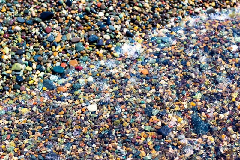 Kleine bunte nasse Steine stockbilder