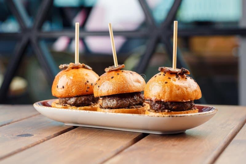 Kleine Burger dienten auf einer Platte als Aperitifs lizenzfreie stockbilder