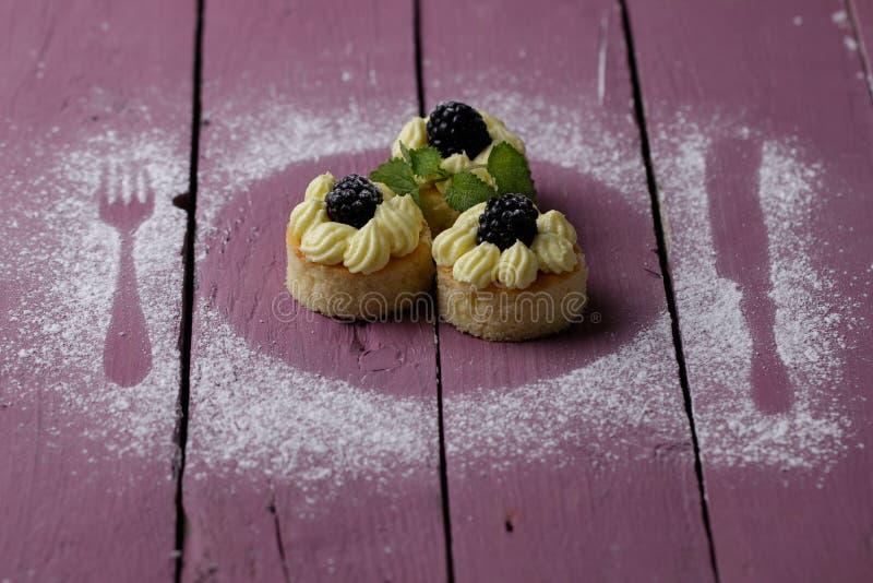 Kleine cakes op de roze houten lijst royalty-vrije stock fotografie
