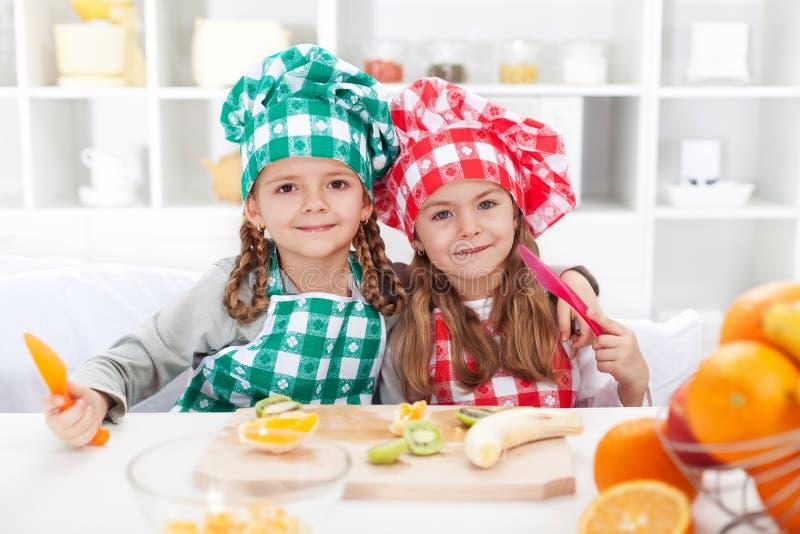 Kleine chef-koks die vruchten in de keuken snijden royalty-vrije stock foto