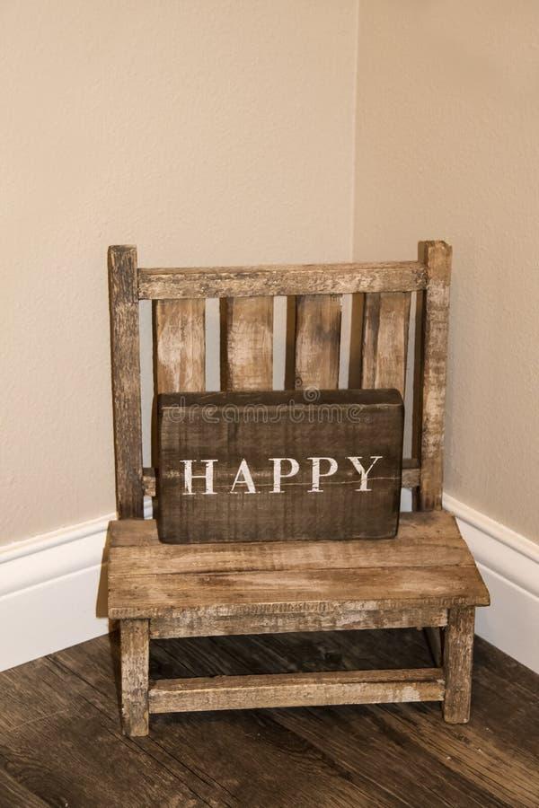 Kleine childs rustikaler Holzstuhl, der in der Ecke eines Raumes mit Holzschild sitzt, das GLÜCKLICHES auf ihm sagt lizenzfreie stockbilder