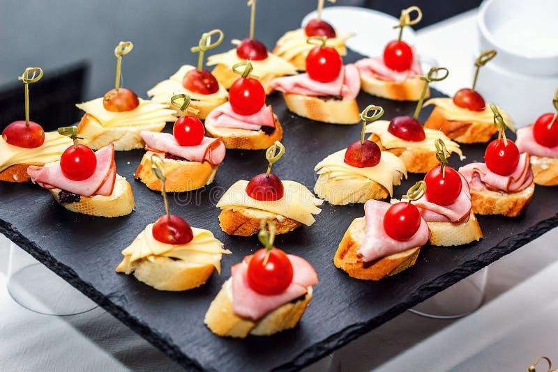 Kleine crostini met geroosterde baguette, kersentomaten, hamplakken, kaas en verse druiven op zwarte achtergrond Sandwiches of as royalty-vrije stock afbeeldingen