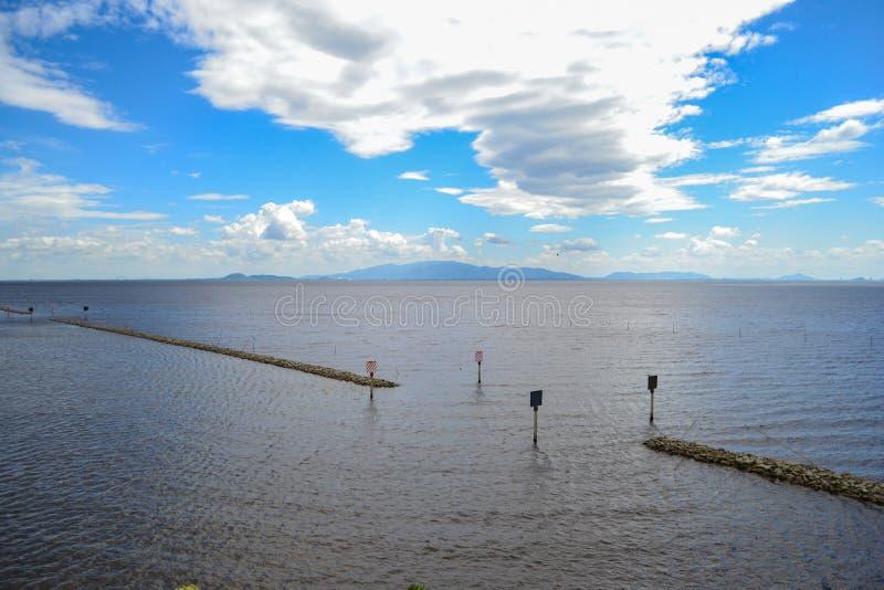 Kleine dammen in het overzees en de blauwe hemel, witte wolken royalty-vrije stock afbeeldingen