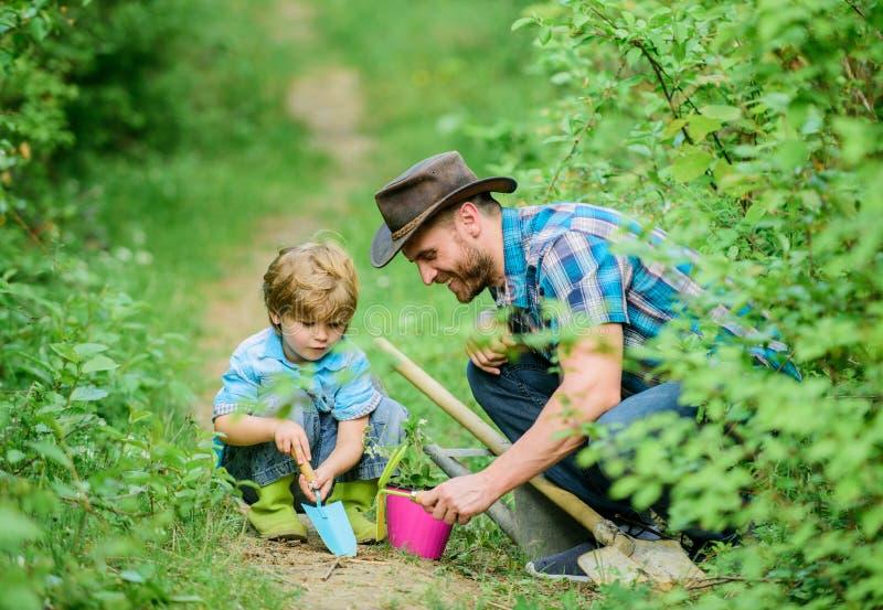 kleine de hulpvader van het jongenskind in de landbouw Ecolandbouwbedrijf vader en zoon in cowboyhoed op boerderij schoffel, pot  royalty-vrije stock afbeeldingen