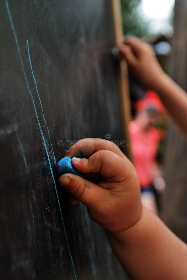 Kleine de tekeningslijnen van de meisjeshand op bord met blauw krijt stock foto's