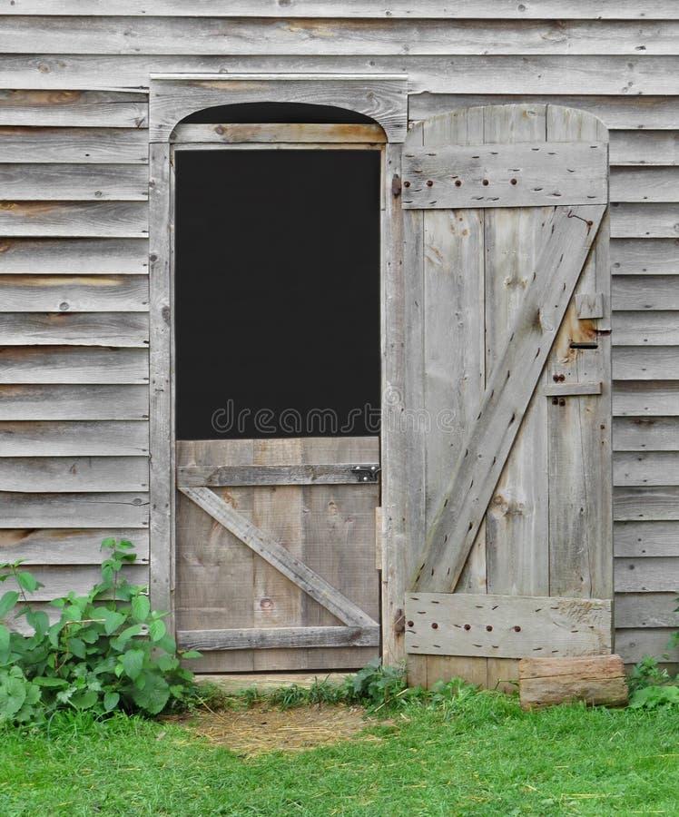 Kleine deuropening in een oude houten schuur royalty-vrije stock fotografie
