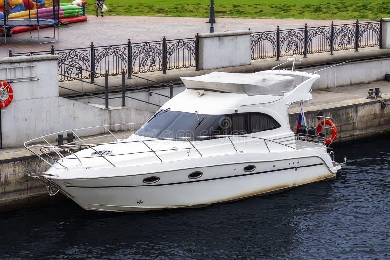 Kleine die motorboot dichtbij drijvende houten pijler wordt vastgelegd royalty-vrije stock foto's