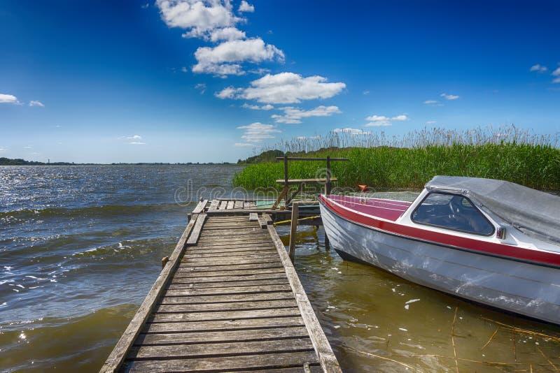 Kleine die motorboot naast een houten pier wordt vastgelegd stock foto