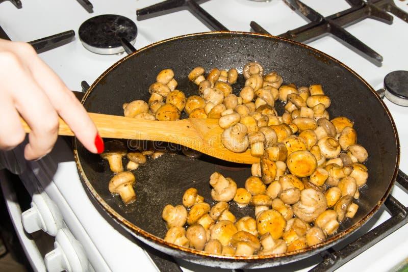 Kleine die paddestoelen in een pan worden gebraden als geheel Gebraden paddestoelen met uien stock foto
