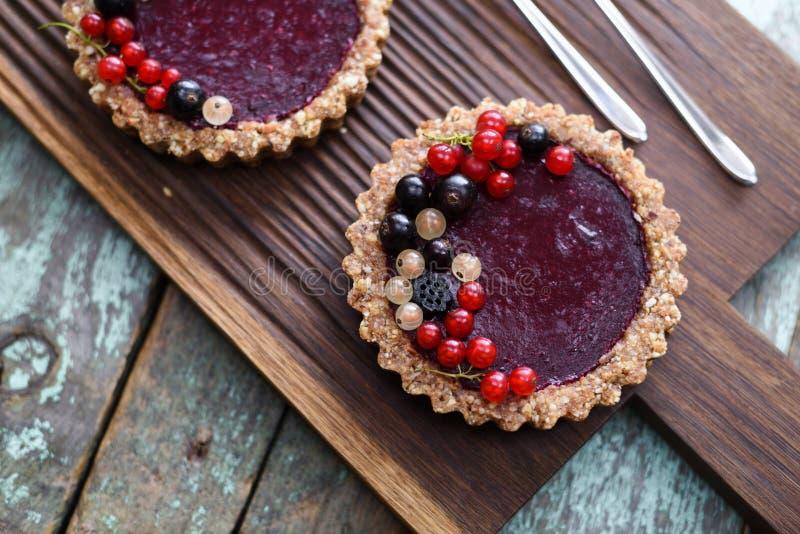 Kleine die veganisttaartjes van noten en bessenjam worden gemaakt met blac wordt verfraaid royalty-vrije stock foto