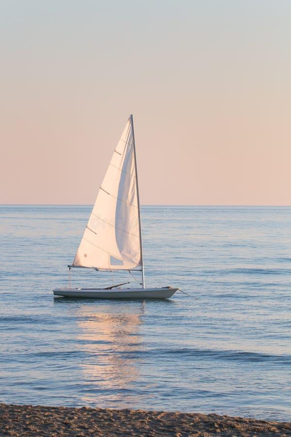 Kleine die zeilboot in het water naast het strand wordt verankerd stock fotografie