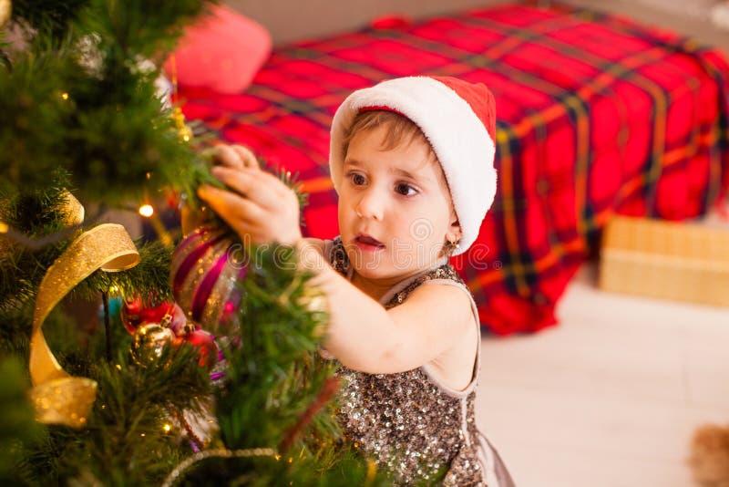 Kleine dochter versiert woonkamer voor Kerstmis royalty-vrije stock afbeelding