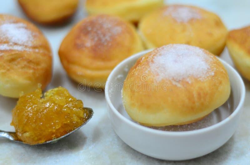 Kleine donuts met suiker en oranje jam stock foto