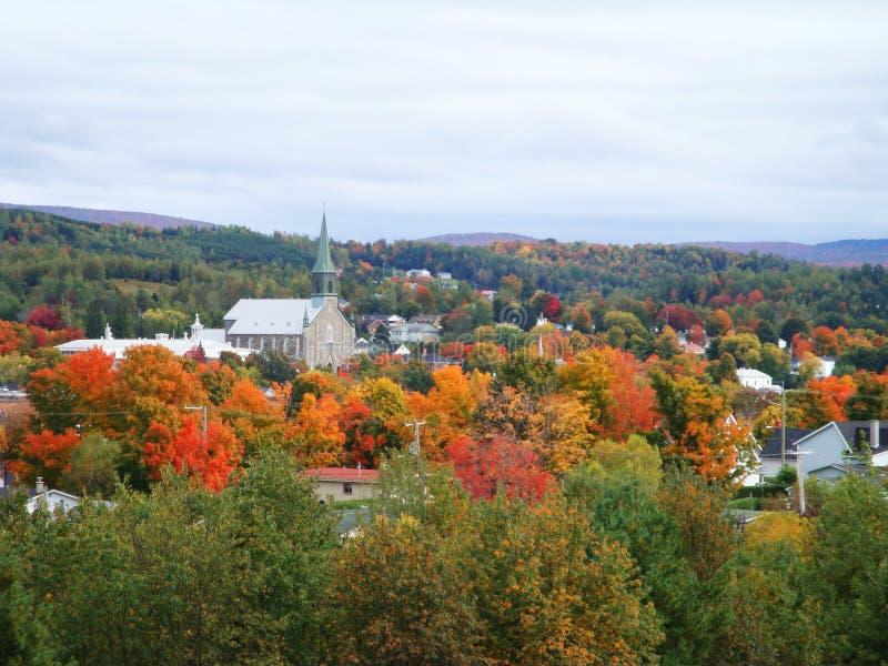 Kleine Dorfkirche umgeben durch helles Herbstlaub in Quebec stockfotos
