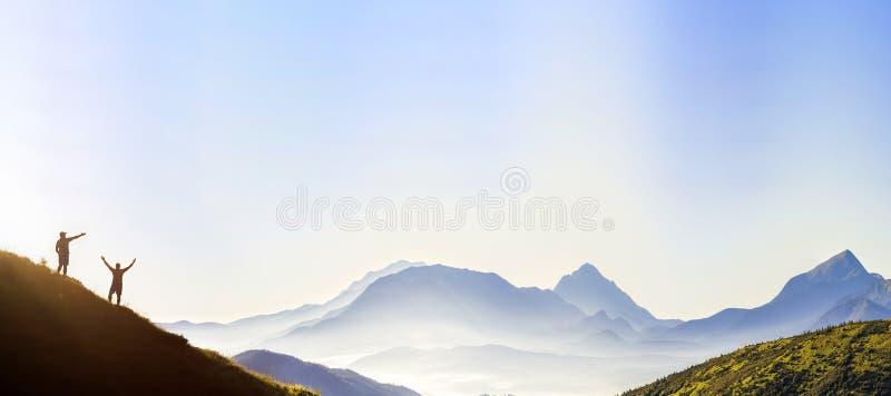 Kleine dunkle Schattenbilder von touristischen Reisenden auf steilem Berghang bei Sonnenaufgang auf dem Kopienraumhintergrund des stockbild